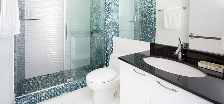 Salle d'eau avec douche à l'italienne au revêtement en zelliges noirs et blancs.