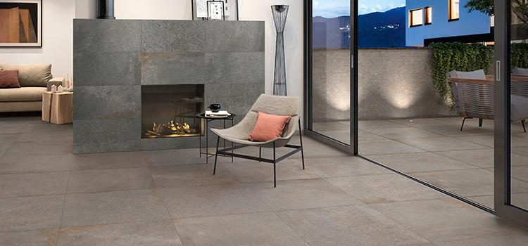 Salon avec cheminée et terrasse au carrelage à grands carreaux couleur taupe
