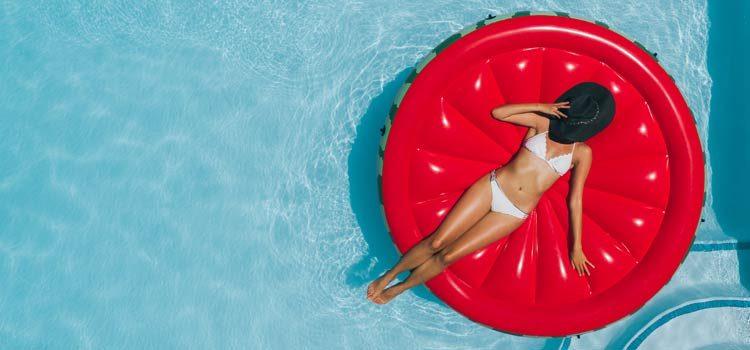 Femme sur une bouée rouge dans un piscine