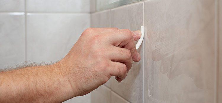 main d'homme qui nettoie les joints du carrelage