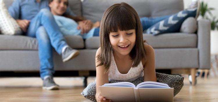 Une enfant qui lit un livre assise sur le carrelage