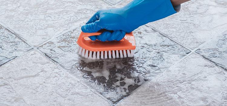personne utilisant une brosse pour gratter le sol