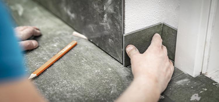 professionnel effectuant la pose de la plinthe en carrelage