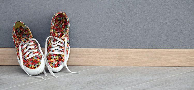 paire de chaussures disposée par dessus la plinthe de carrelage