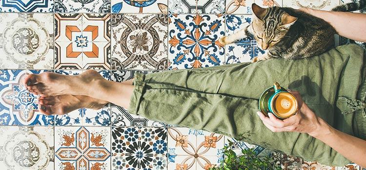 Femme et son chat assis sur un carrelage mosaïque
