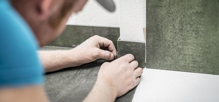Professionnel effectuant la pose de la plinthe de carrelage