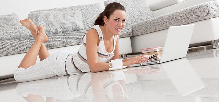 jeune femme utilisant son PC portable installée sur son carrelage